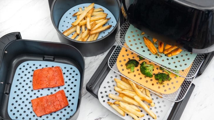 3 air fryers with silicone mats on the baskets or trays