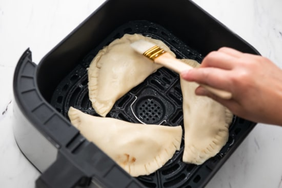 Brushing hand pie in air fryer with egg wash