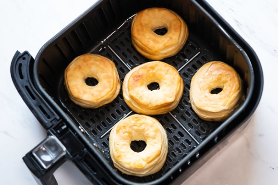 Cooked doughnuts in air fryer basket