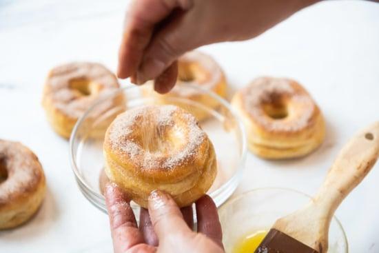 Dusting doughnut with cinnamon sugar