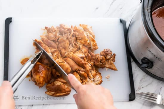 Cutting up chicken on a board