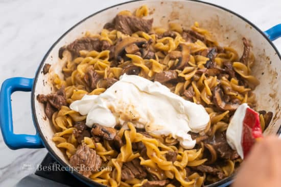 Stirring in sour cream to cooked noodles and beef