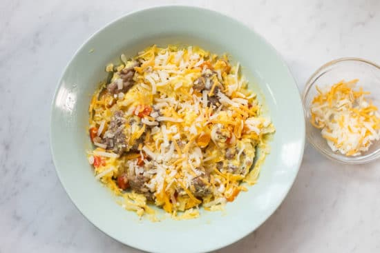 Cheese added on top of cooked eggs and sausage