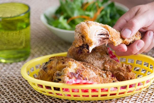 Baked Fried Chicken Recipe in basket holding drumstick
