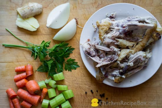 Chicken bones and vegetables on cutting board